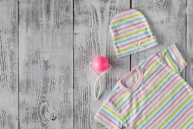 Baby shirt on wooden desktop. mock up