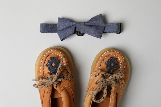 Детская обувь и галстук-бабочка на светло-сером фоне.
