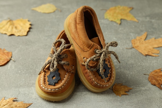 Детская обувь и листья на сером текстурированном фоне.