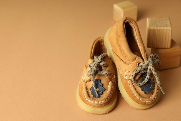 Детская обувь и деревянные кубики на бежевом фоне.
