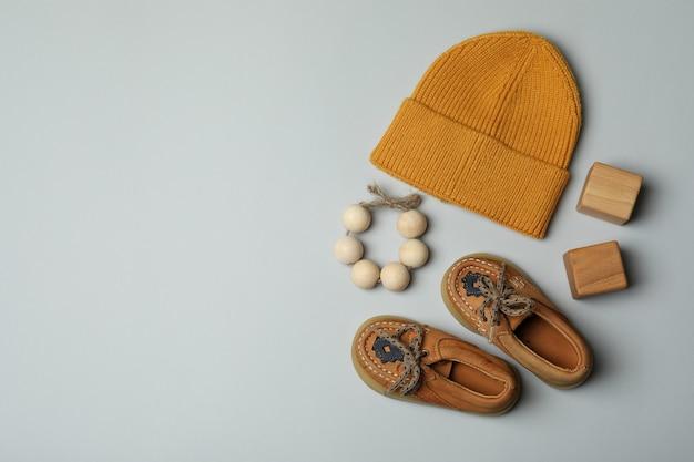 Детская обувь, шапка и игрушки на светло-сером фоне.