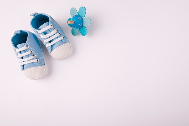 Baby shoes and pacifier copy space