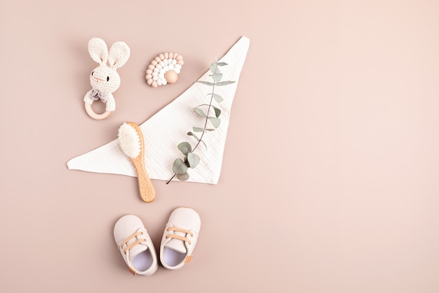 Baby shoes rattle and teether on neutral background. organic newborn gifts branding small business idea. baby shower invitation greeting card. flat lay top view