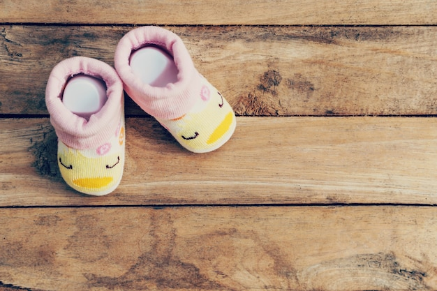Baby shoes on wooden background with space