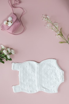 Baby shower flower background with baby girl accessories on pink background with copy space for text, top view, flat lay