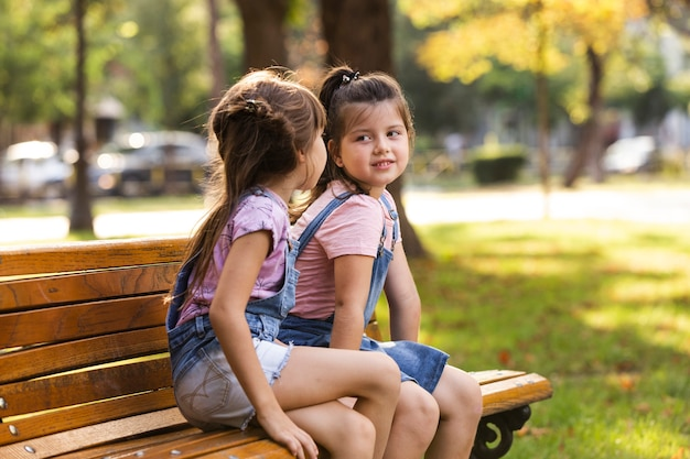 Baby sisters sitting on a bench outdoors