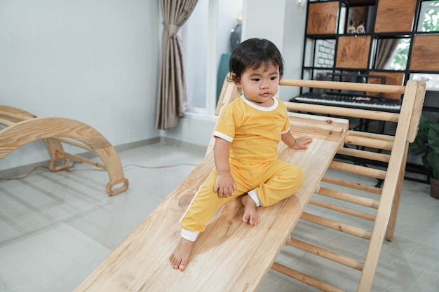 Baby sits alone on the slide while playing in the pikler triangle toy in the living room