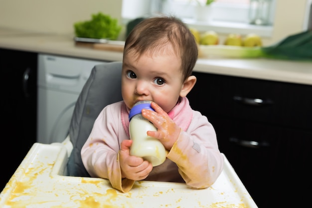 The baby sits in a children's chair and drinks milk from a bottle.
