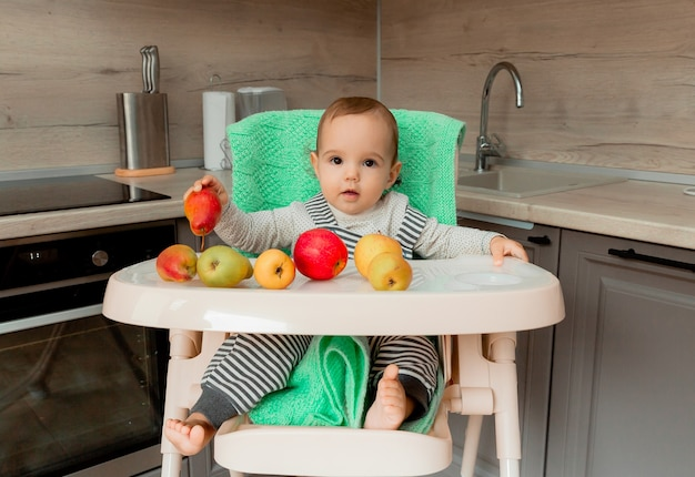 Baby sits in a highchair and eats fruit.
