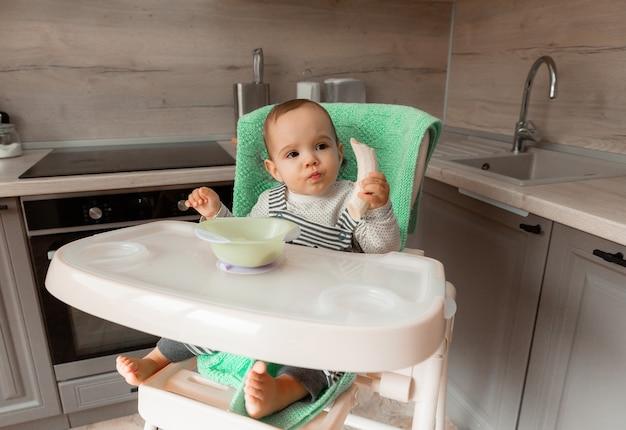 赤ちゃんは台所の高い椅子に座ってバナナを食べます。