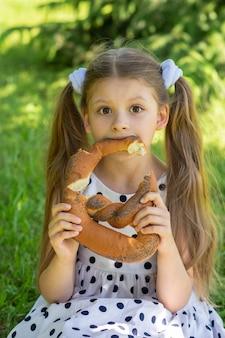 아기는 풀밭에 앉아서 신선한 공기 속에서 양귀비 씨가 든 베이글을 탐욕스럽게 먹습니다.