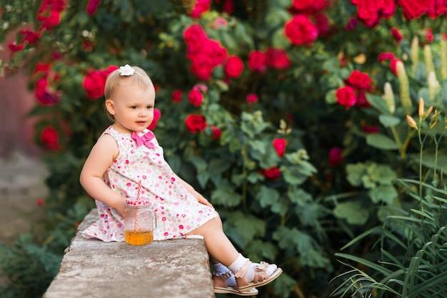 Ребенок сидит с чашкой сока на фоне красных роз