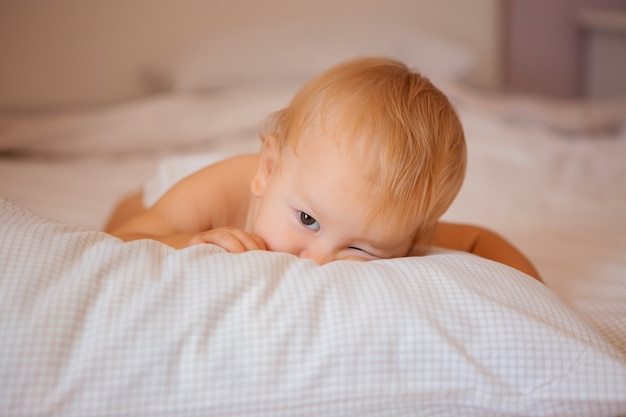 Baby sitting in bed on bed linen in diapers