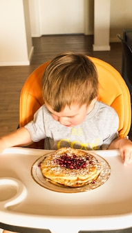 Baby sitting on high chair looking at pancake on plate