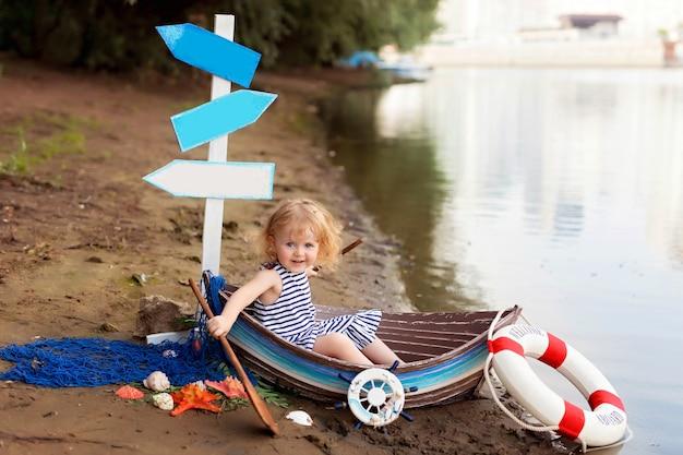 海沿いの貝殻を持つ砂浜で船乗りに扮したボートに座っている赤ちゃん
