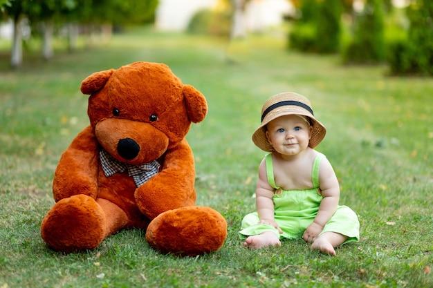 큰 테 디 베어와 함께 여름에 푸른 잔디 잔디밭에 앉아 아기