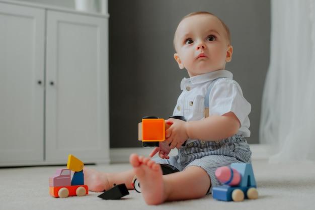 아기는 장난감으로 바닥에 앉아 놀랐습니다.
