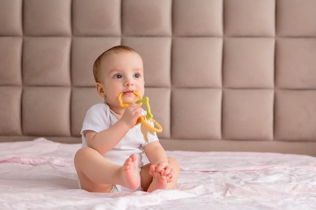 Baby sitting with a toy in the bedroom on the bed