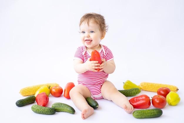 흰색 배경에 야채와 함께 앉아 있는 아기는 첫 번째 미끼의 개념을 분리합니다