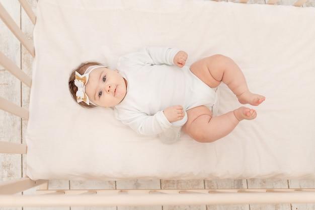 白いボディースーツの水のボトルと一緒にベッドで6ヶ月の赤ちゃん