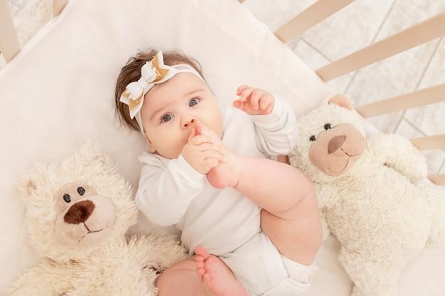 6か月の赤ちゃんは、テディベアと一緒に白いボディースーツを着たベビーベッドに横たわり、足を吸います