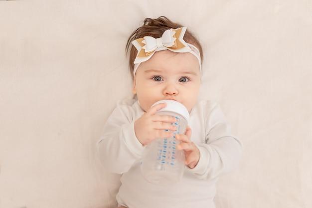 6か月の赤ちゃんは、ボトルを持ったベビーベッドに横たわり、白いボディスーツで水を飲みます