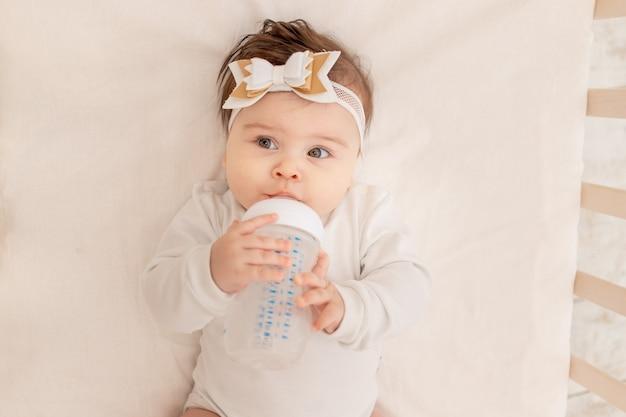 Малыш полгода лежит в кроватке с бутылкой и пьет воду в белом боди.