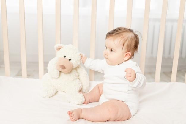 テディベアと白いボディスーツのベビーベッドで遊ぶ6ヶ月の赤ちゃん