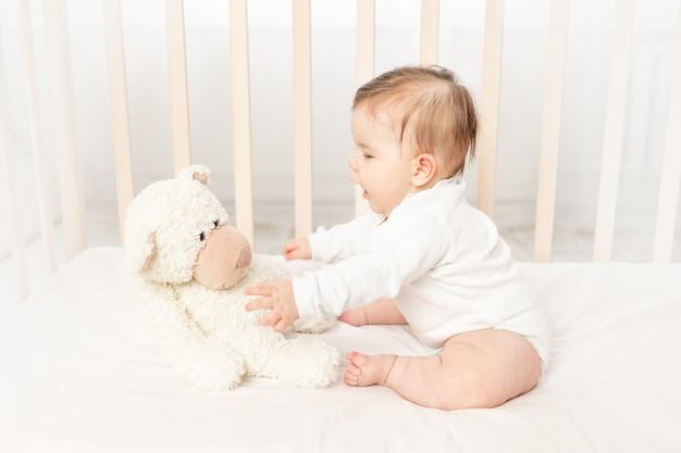 Малышка шесть месяцев играет в кроватке в белом боди с мишкой тедди