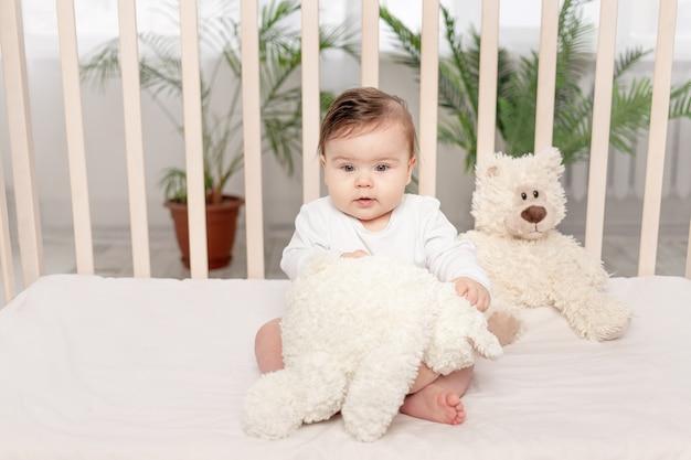Ребенок шести месяцев играет в кроватке в белом боди с мишкой тедди