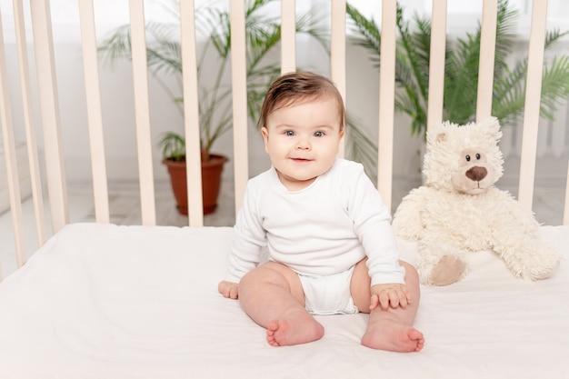 Малышка полгода сидит в кроватке в белом боди с игрушками мишки тедди
