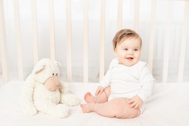 장난감이 있는 흰색 바디수트를 입고 유아용 침대에 앉아 있는 6개월 아기 테디베어