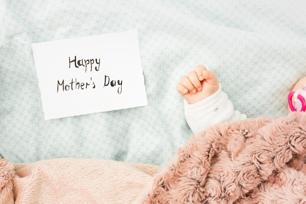 Baby sleeping in bed near happy mothers day inscription