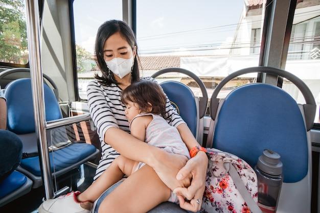 公共バスで母親の膝の上で寝ている赤ちゃん