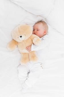 Baby sleeping while holding a teddy bear