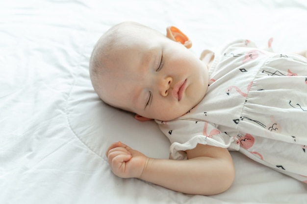 Baby sleeping on a white bed