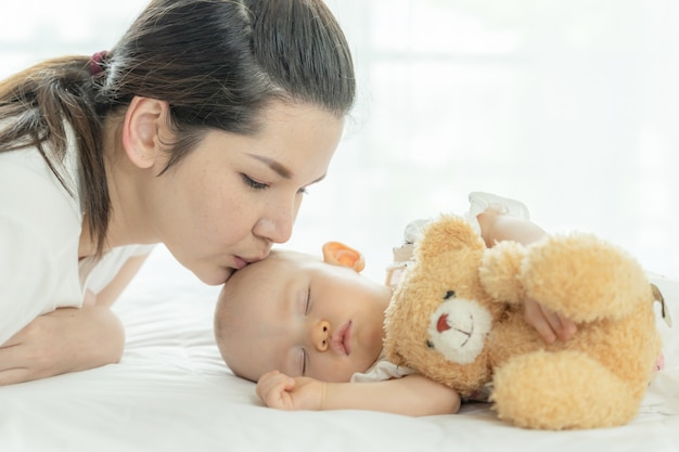 Baby sleeping with a teddy bear and mother kissing her