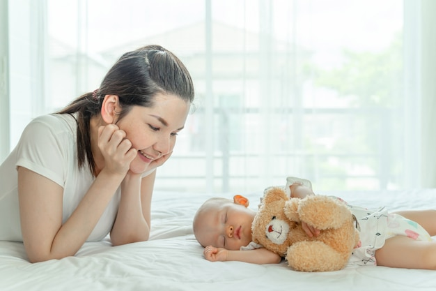 Baby sleeping with a teddy bear and mother looking at them
