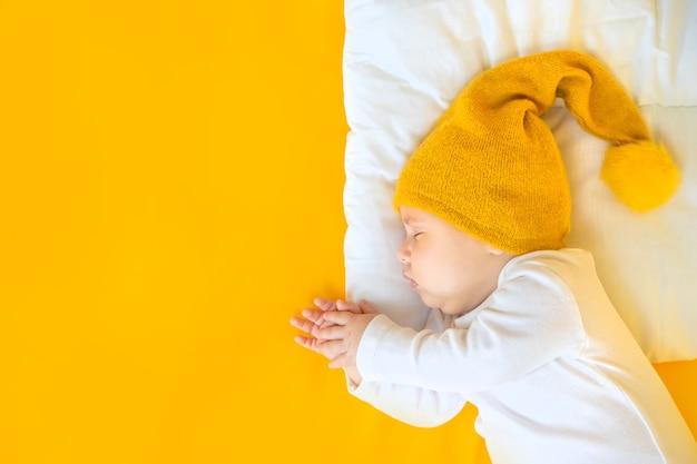 아기는 노란색 배경, 겨울 및 휴가 개념에 모자와 함께 잔다