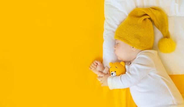 Ребенок спит в шляпе на желтом фоне, концепция зимы и праздника