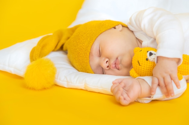 Baby sleeps with hat on a yellow background, winter and holiday concept