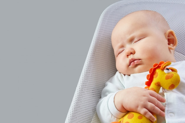 Baby sleeps with an orange toy giraffe in a deck chair on a gray wall with copy space