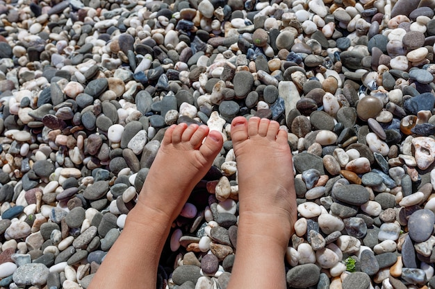 여름 휴가철 바다 해변의 돌 배경에 어린 아이의 작은 발이 가까이 있다
