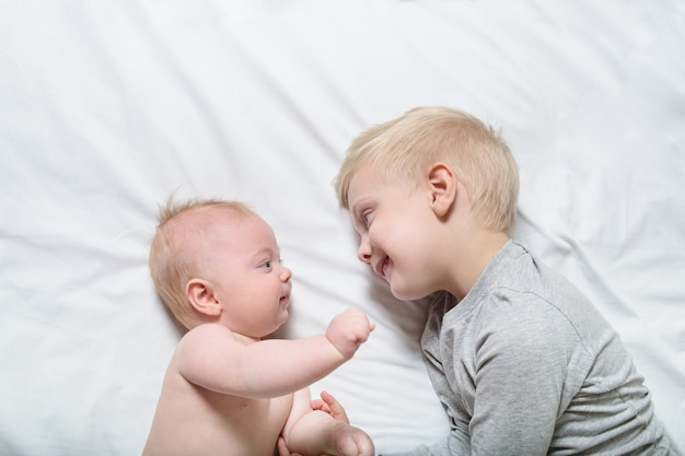 Baby and smiling older brother are lying on the bed. they play, communicate and interact. top view