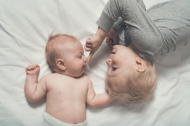 Baby and smiling older brother are lying on the bed