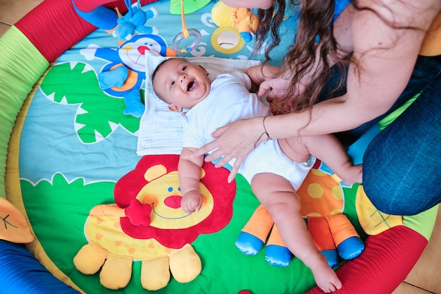 Baby smiling while playing with his mother on the floor at home.