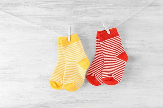 Детские носки, висящие на веревках на деревянных фоне