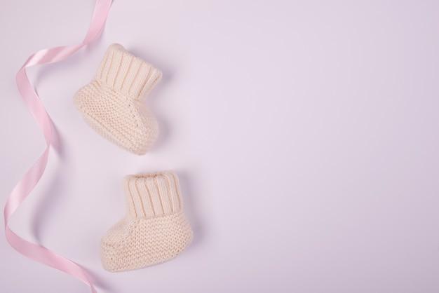 Baby socks with pink ribbon flat lay