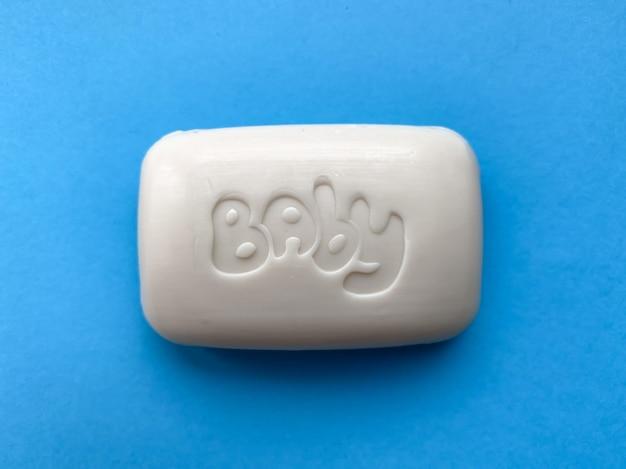 青い背景の手のためのベビー固形石鹸。衛生とケア。