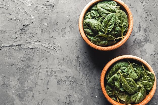 Детские листья шпината в шаре на сером бетонном фоне. чистое питание, детокс, диетический пищевой ингредиент